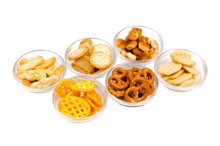 Bowls of pretzels on glass on white background 免版税图像