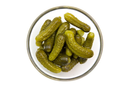 pickles on bowl on white background seen from above