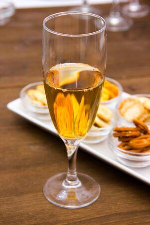 Fluit met aperitief en pretzels op houten tafel gezien close