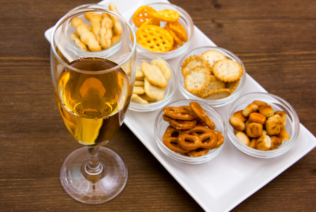 Flute with aperitif and pretzels on wooden table