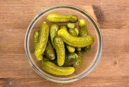 Pickles on bowl on wooden table seen from above
