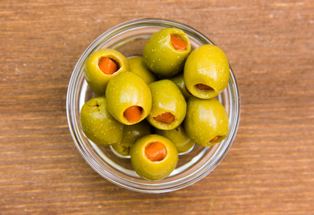 Stuffed olives in bowl on wooden top views