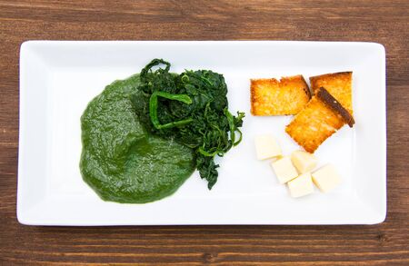creamed: Tray with creamed spinach and croutons on wooden table seen from above Stock Photo