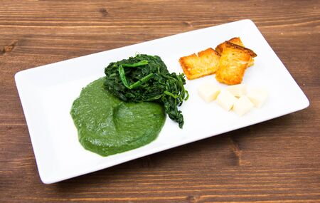 creamed: Tray with creamed spinach and croutons on wooden table Stock Photo