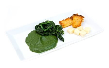 creamed: Tray with creamed spinach and croutons on a white background