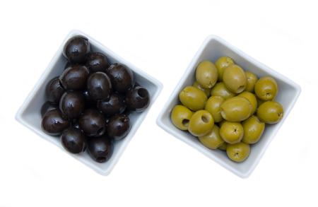 Bowls with green and black olives on a white background seen from above