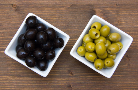 Bowls with green and black olives on wooden table top views