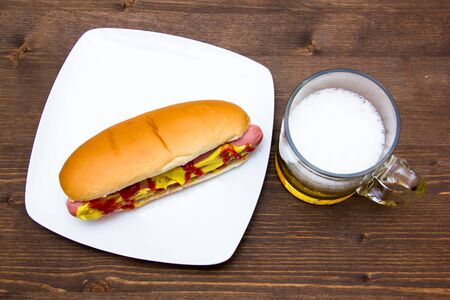 hotdog sandwiches: Beer and hot dogs on wooden table seen from above