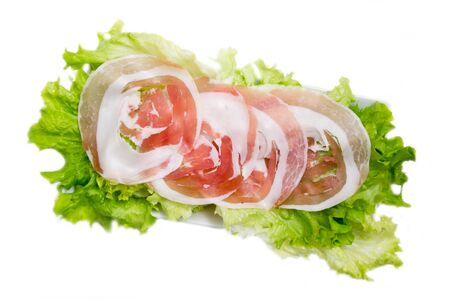Rolled bacon on salad on white background top view