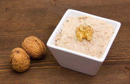 Walnut pesto on bowl on wooden table photo