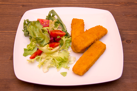 fishfinger: Fish fingers with salad on wooden table Stock Photo