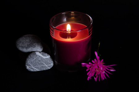 scented candle: Scented candle with flower and stones on a black background