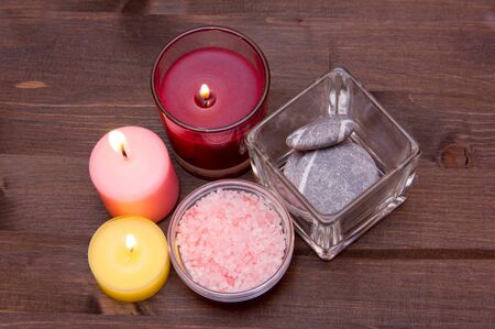 perfumed candle: Candles and bath salts on wooden table seen from above