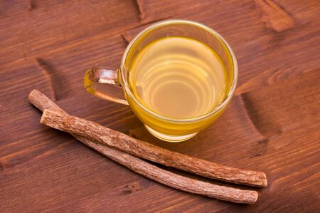 licorice: Cup of herbal tea licorice in wooden table top view Stock Photo