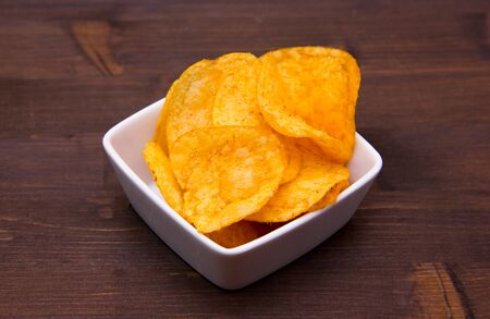 Chips paprika on square bowl on wooden table