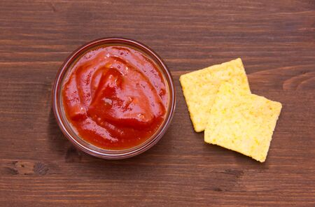 corn chips: Spicy salsa with corn chips on wooden table top view