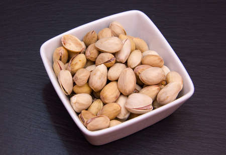 pistachios: Pistachios on a square bowl on slate top