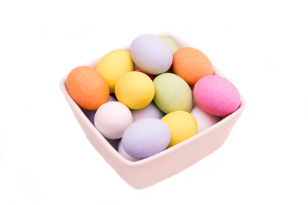 backgraound: Colored eggs on a square bowl on a white background