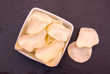 person appetizer: Krupuk on a square bowl on slate top top views Stock Photo