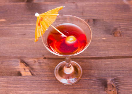 Red cocktail with umbrella on a wooden table seen from above