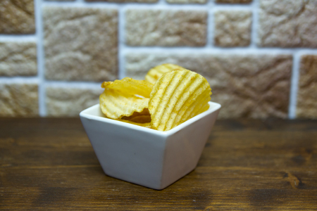 Corrugated chips inside square bowl on a wooden table viewed from close up