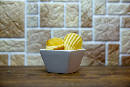 Corrugated chips inside square bowl on a wooden table