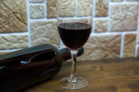 Glass of wine and a bottle on a wooden table 免版税图像