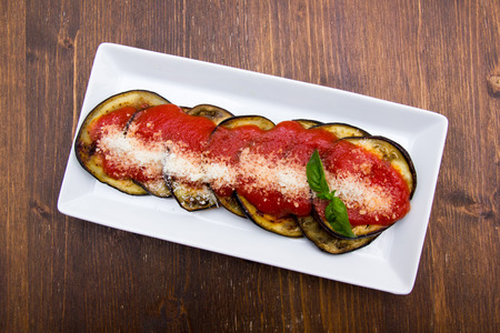 Eggplant parmigiana on a wooden table seen from above
