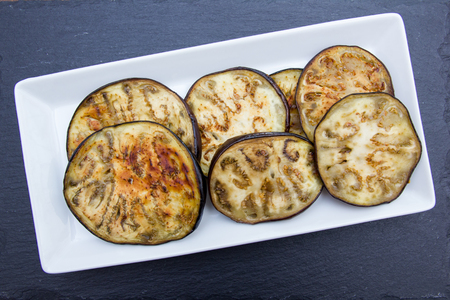 Slices of aubergine on a slate top viewed from above
