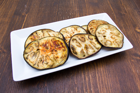Slices of aubergine on tray on a wooden table