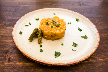 Risotto with asparagus cream on a wooden table