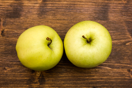 Two yellow apples on a wooden table viewed from above