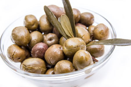 Bowl with olives and olive branch on a white background seen close up