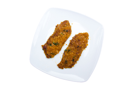 Breaded slices of meat on a plate on a white background viewed from above Banque d'images