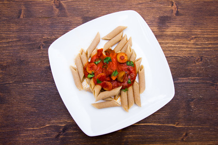 Pasta with tomato sauce and olives on a wooden table top view