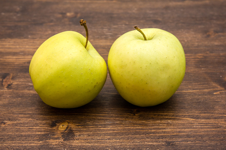 Two yellow apples on a wooden table