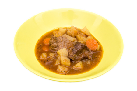 Stew of meat and vegetables on a white background