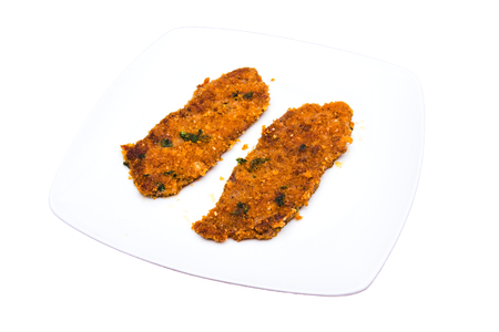 Breaded slices of meat on a plate on a white background