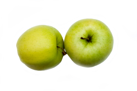 Two yellow apples on a white background viewed from above