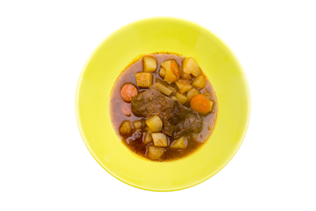 Stewed meat and vegetables on a white background seen from above