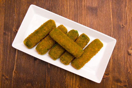 Spinach sticks on a tray on a wooden table viewed from above