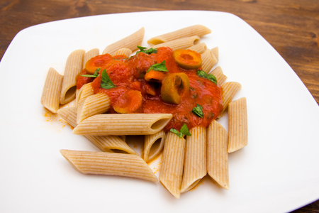 Pasta with tomato sauce and olives on a wooden table close up view