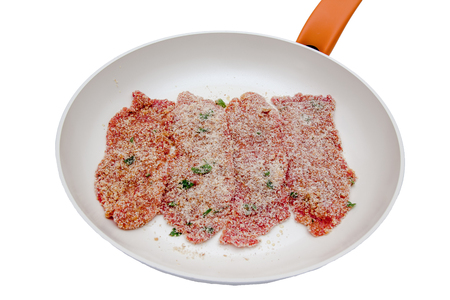 Slices of breaded raw meat in a pan on a white background