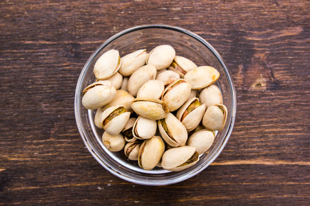 Pistachios on bowl on a wooden table viewed from above