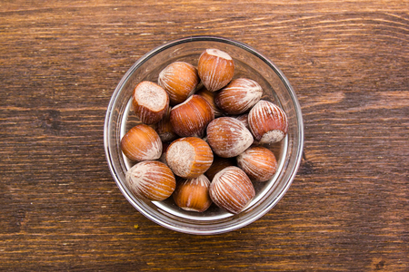 Hazelnuts on bowl on a wooden table viewed from above