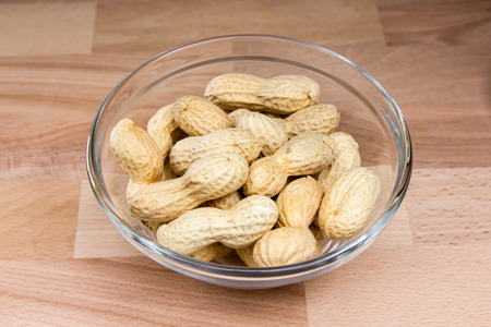 Peanuts on bowl on a wooden beech table