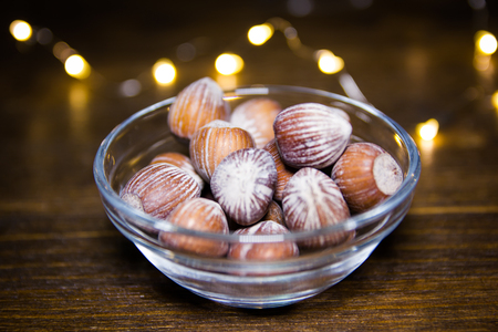 Hazelnuts on bowl on a wooden table with blurred lights in the background 免版税图像