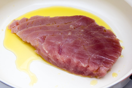 Raw tuna slice with oil in pan close up view
