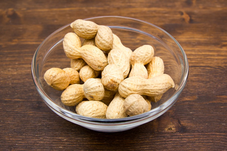 Peanuts on bowl on a wooden table