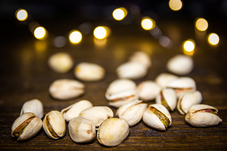 Pistachios on a wooden table with blurred lights in the background 免版税图像 - 118089363